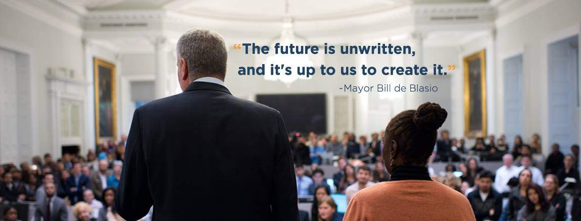 "Mayor De Blasio and First Lady Chirlane McCray look out onto City Hall employees. Picture text reads, ""The future is unwritten, and it's up to us to create it."""