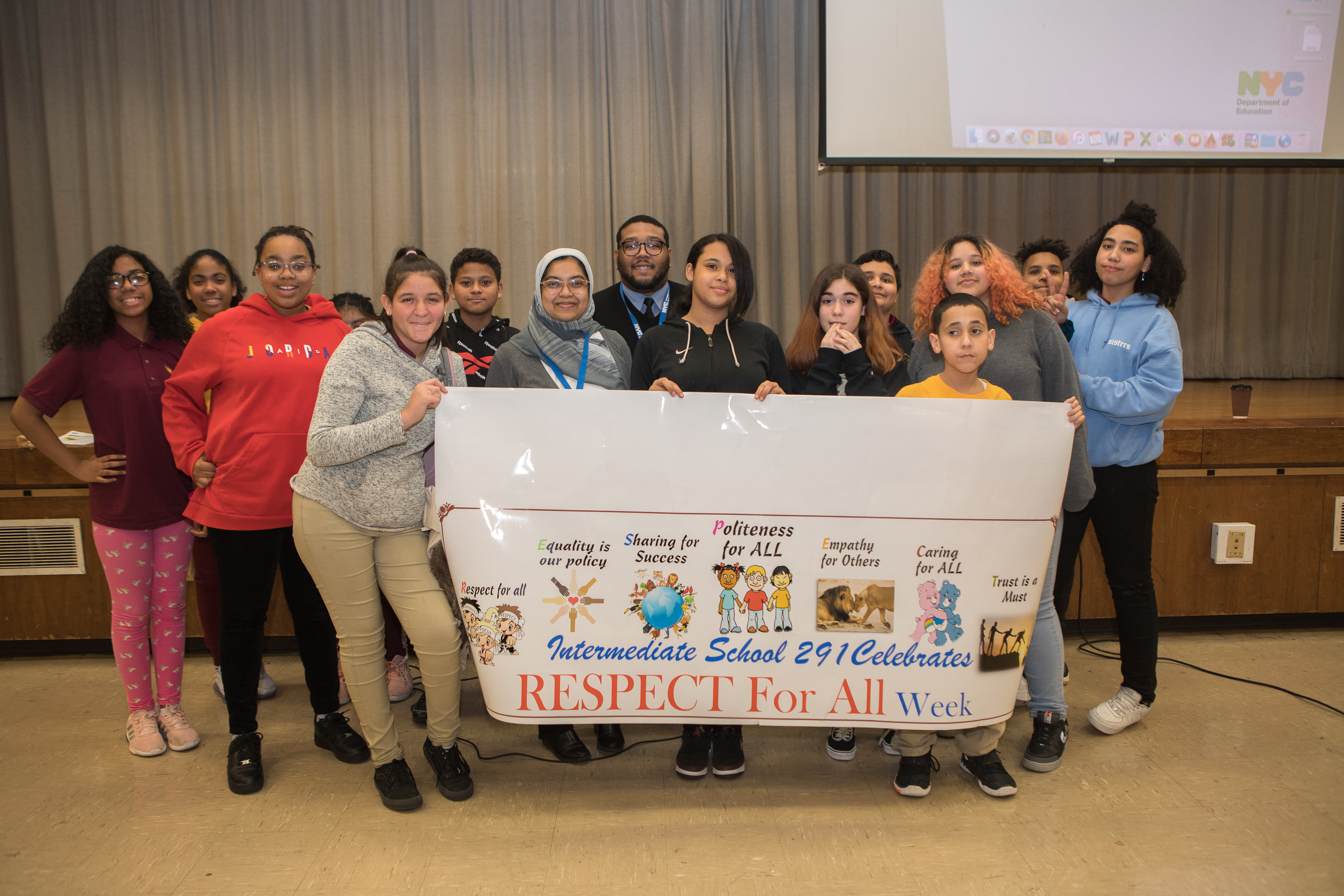 "Group of young people with Commission staff members posing for camera holding up a banner that reads ""Intermediate School 291 Celebrates Respect for All Week."""