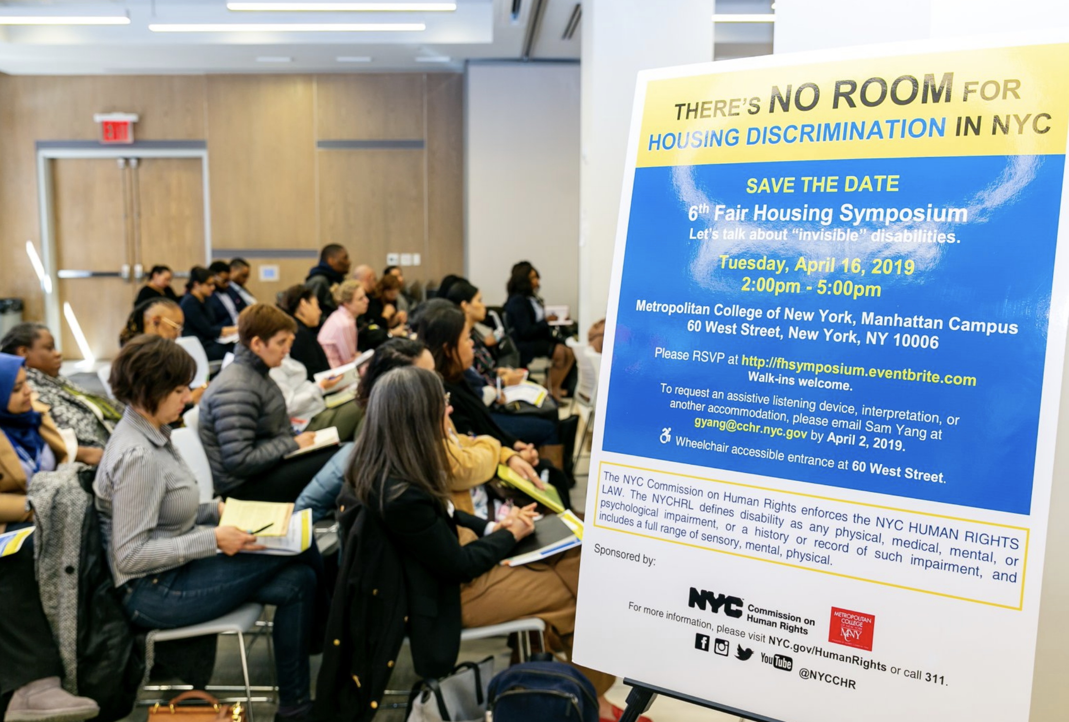 "Profile of audience sitting at event next to a sign that reads: ""There's No Room For Housing Discrimination in NYC,"" 6th Fair Housing Symposium, Tuesday, April 16, 2019."