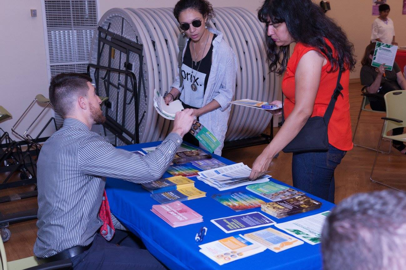 Commission staff member sitting at a table with materials, distributing literature to two New Yorkers.