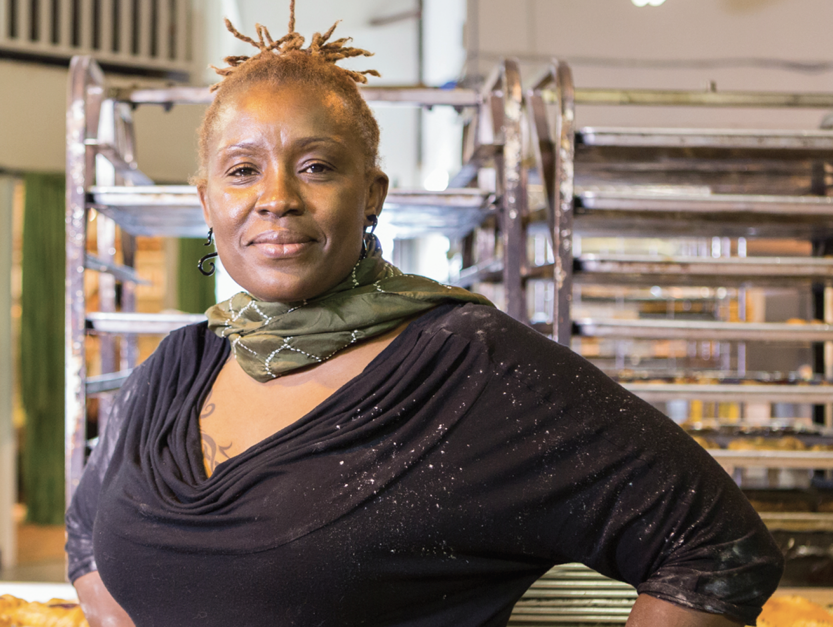 African American  woman looking into camera with a half-smile, with racks of food trays behind her.