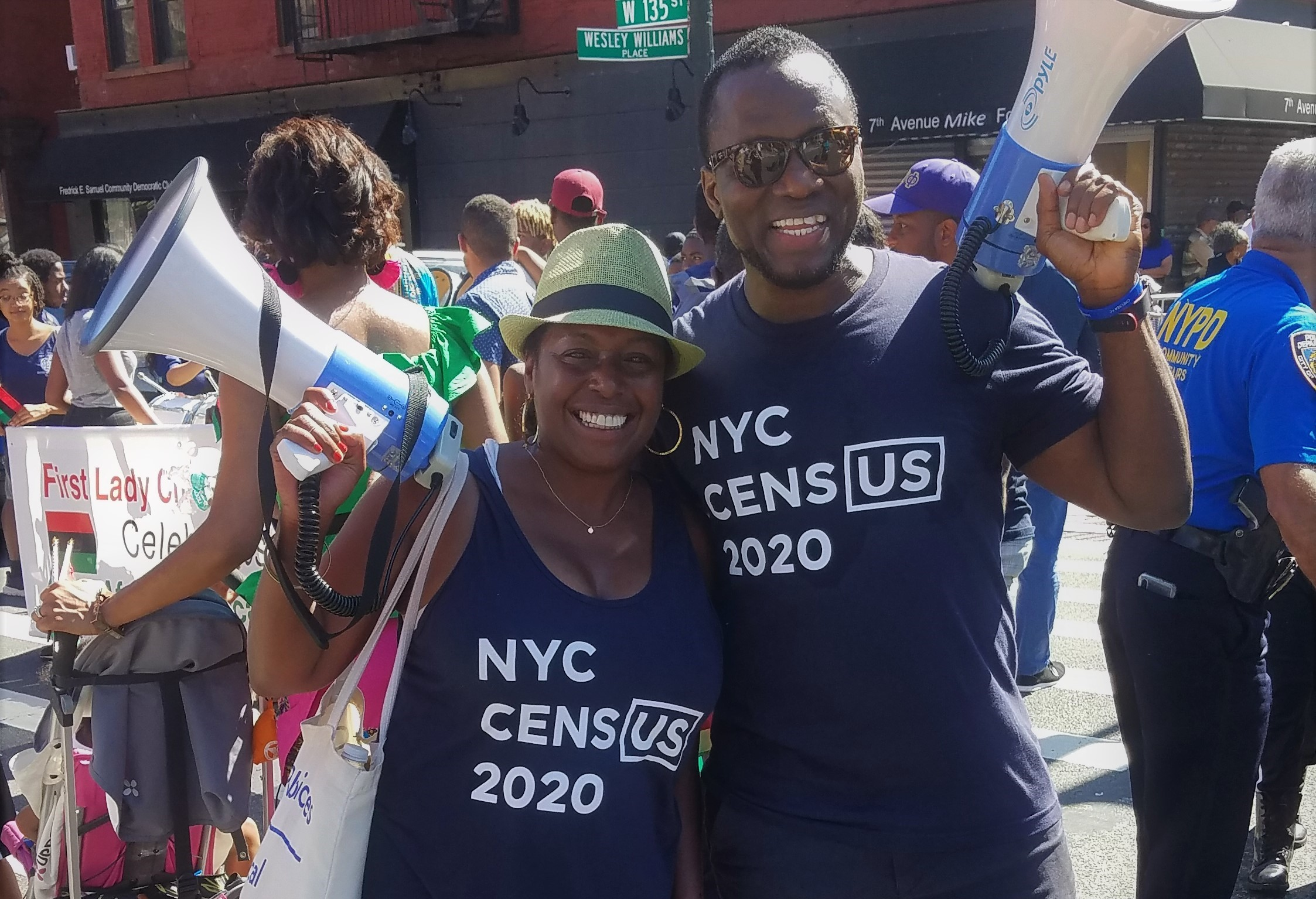 Two smiling volunteers holding megaphones, wearing t-shirts that says NYC Census 2020.