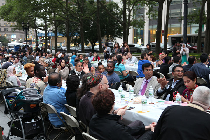 Group of people sitting at table at Community Iftar in the Streets Spring 2017 listening to speaker