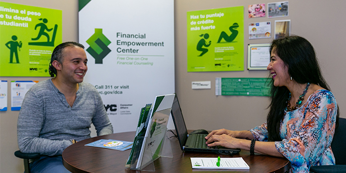 Happy Financial Empowerment Center counselor and client during a coaching session with background featuring the Financial Empowerment Center logo banner and ads