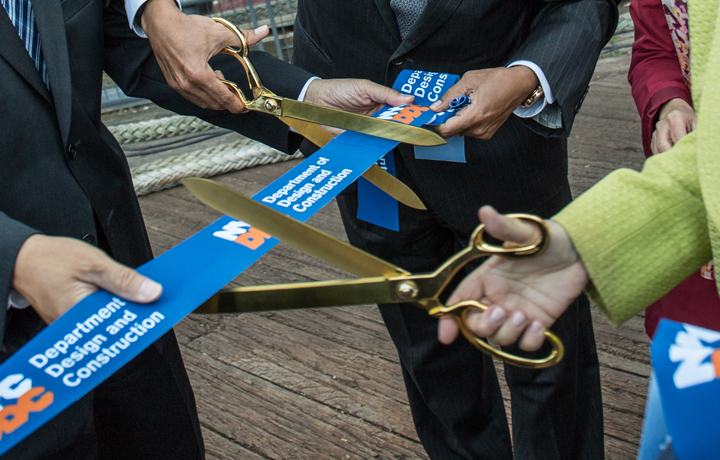 Two golden scissors cutting a ddc ribbon
