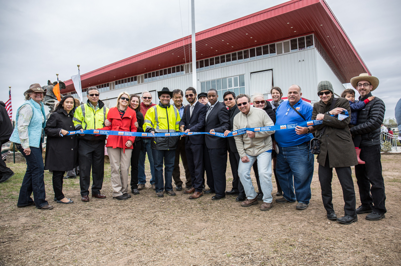 DDC staff prepare to cut the ribbon. The Riding Center is in the background.