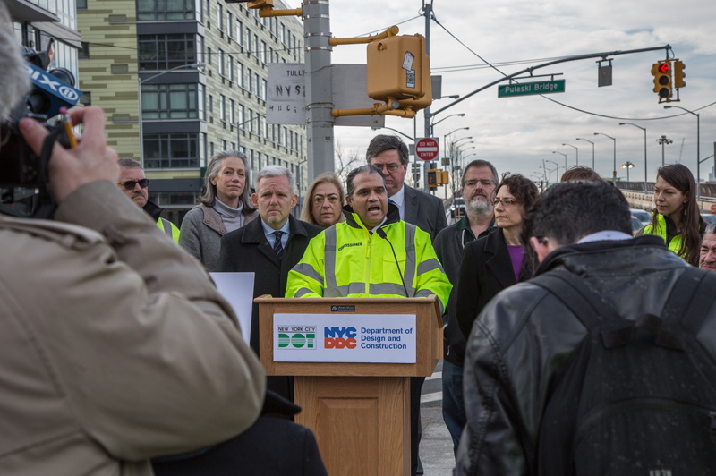 Commissioner Peña-Mora speaks behind a podium at an intersection in LIC.