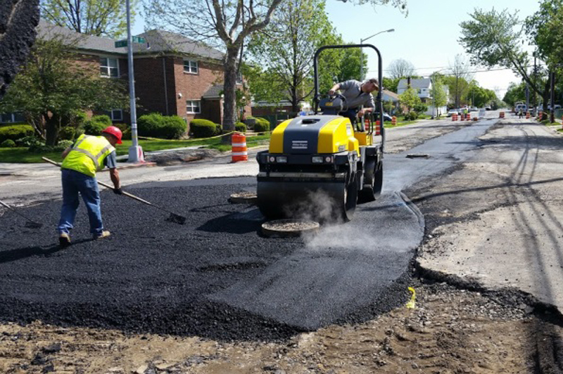 Crews work to spread asphalt on a road.