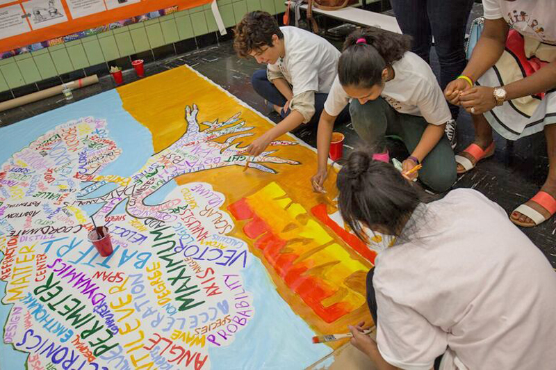 Three people sit on the floor and paint on a large piece of paper for a mural.
