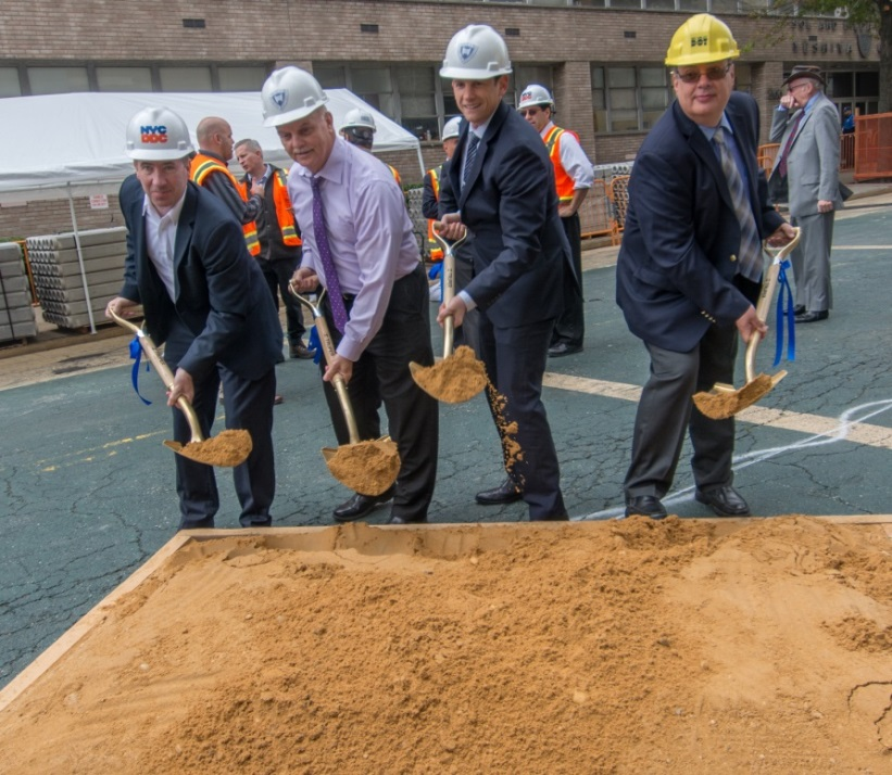 Four employees from DDC, DOT and Yeshiva University performing the ceromonial groundbreaking