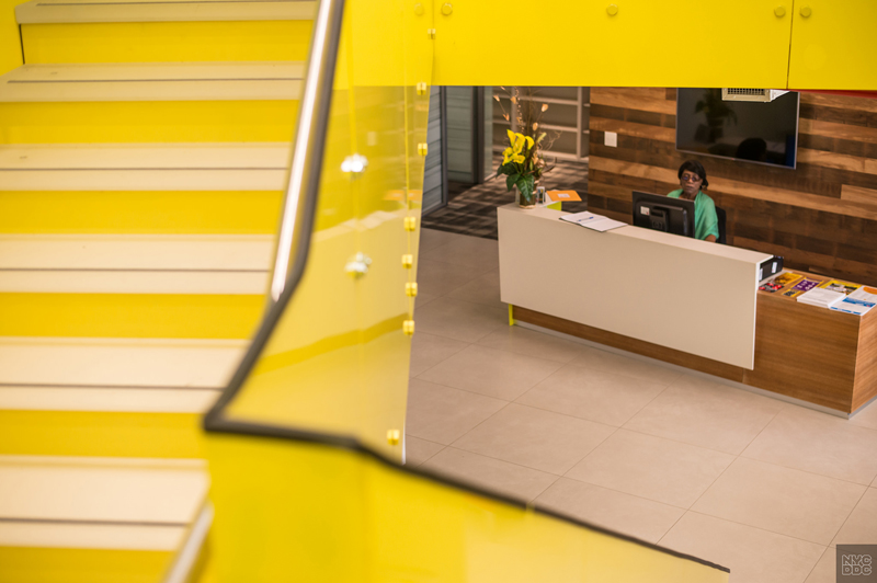 a yellow staircase frames the view of a woman working at an entrance desk.