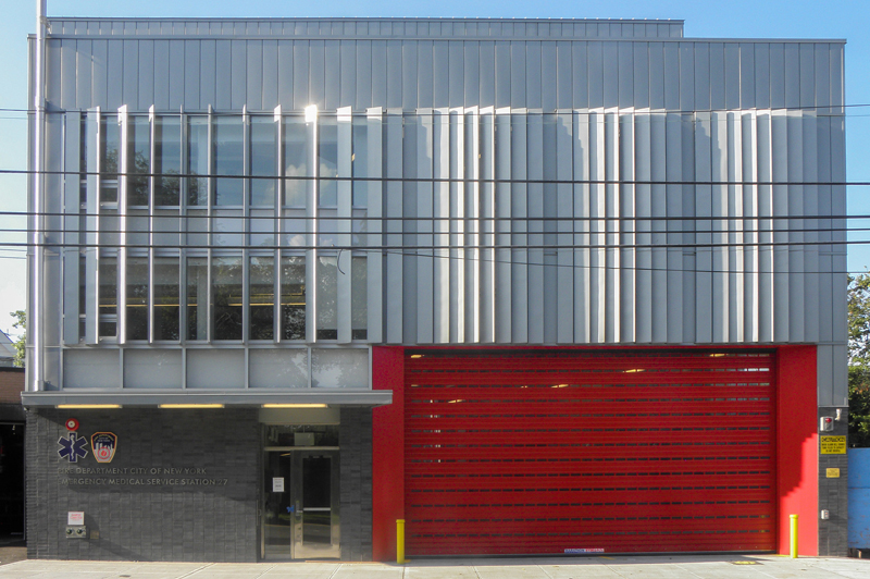 The facade of EMS 27. A bright red garage door, surrounded by metal facing.