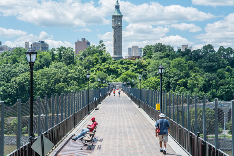 A view across the High Bridge. Pedestrians stroll and sit on benches.