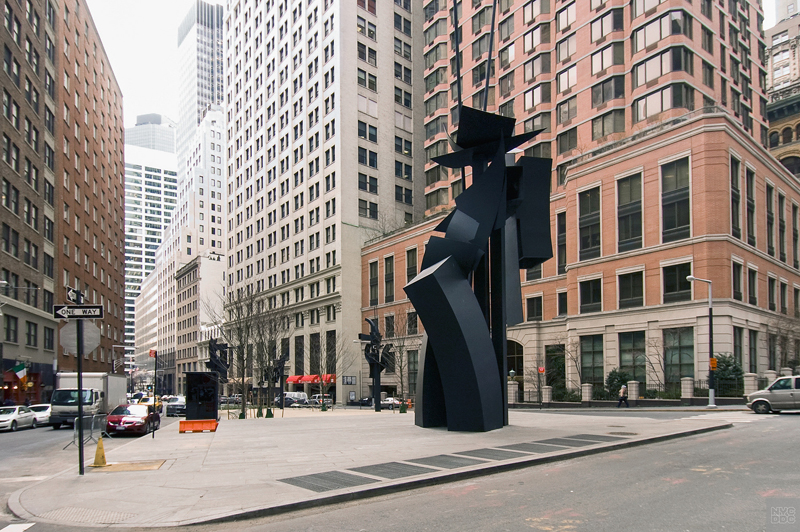 View of a tall, black sculpture in the middle of Louise Nevelson Plaza