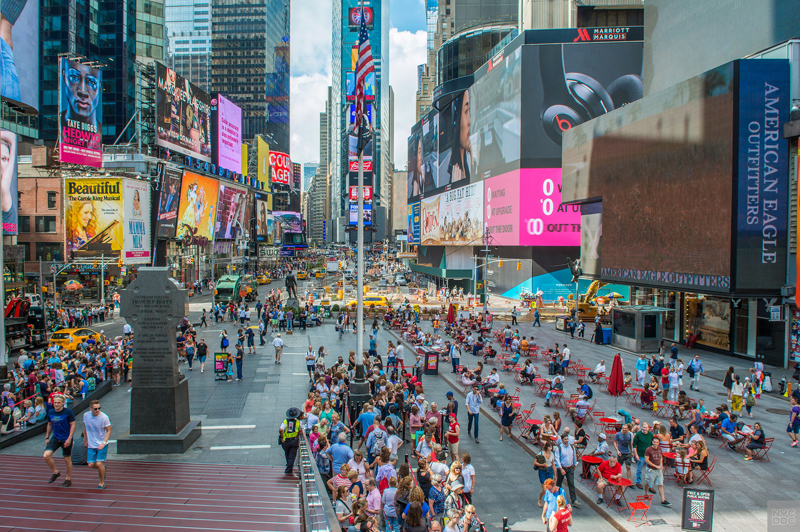 A view from the top of the TKTS booth in Times Square. Pedestrians are sitting at red tables.