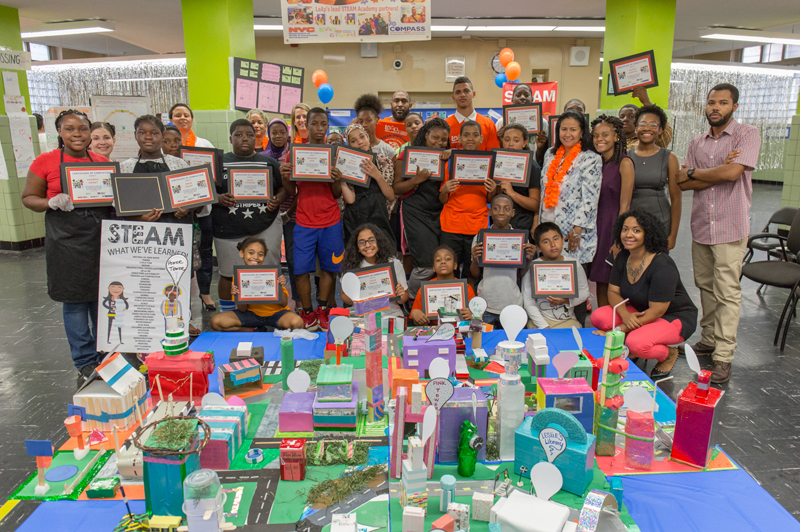 A group of Bronx middle school students pose behind a colorful paper model of a city.