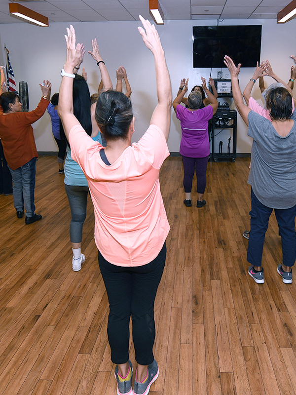 A group of older adults taking a fitness class stretch their hands up to the ceiling.
