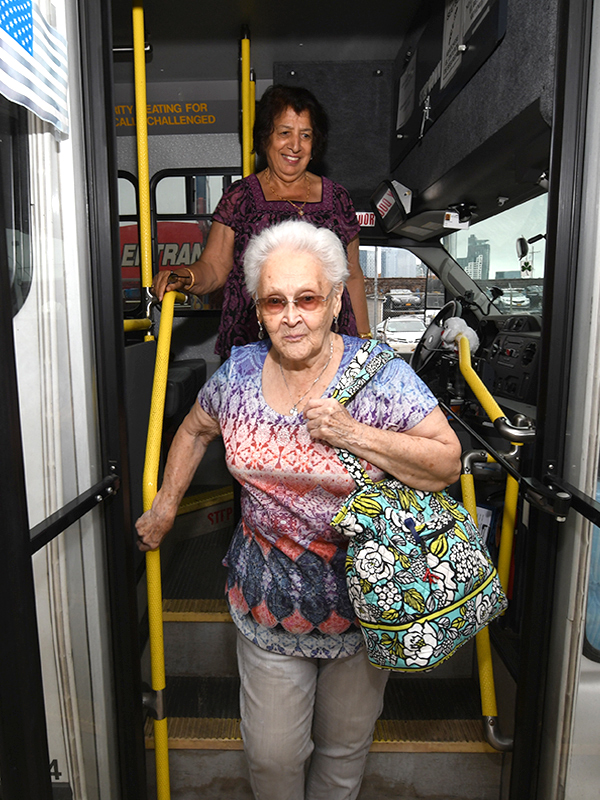 An older women gets off a bus while holding a bright yellow hand railing.