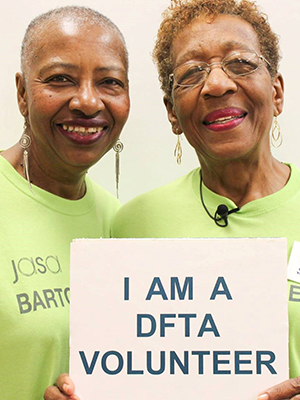 "Two smiling female volunteers hold a sign that reads, ""I am a DFTA volunteer."""
