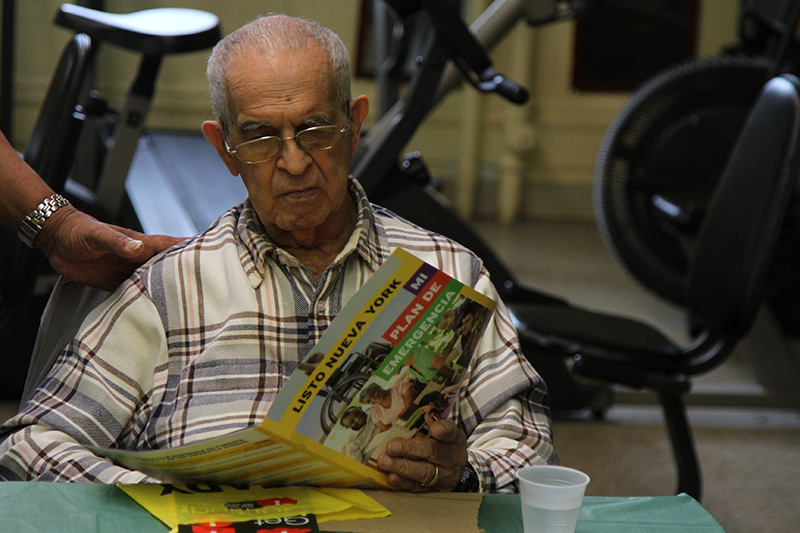 An elderly man reading an emergency preparedness brochure