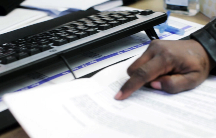 Man pointing at paperwork in front of a computer keyboard