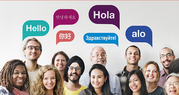 "Photograph of 13 people standing together with five speech bubbles above their heads. Text reads ""hello"" in different languages."