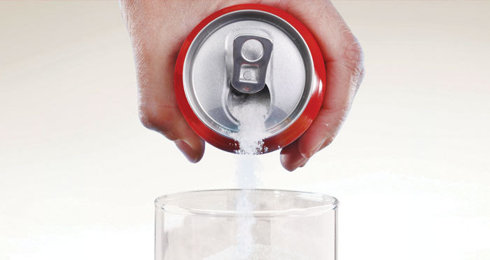Photograph of a hand holdinga soda can pouring sugar into a drinking glass.