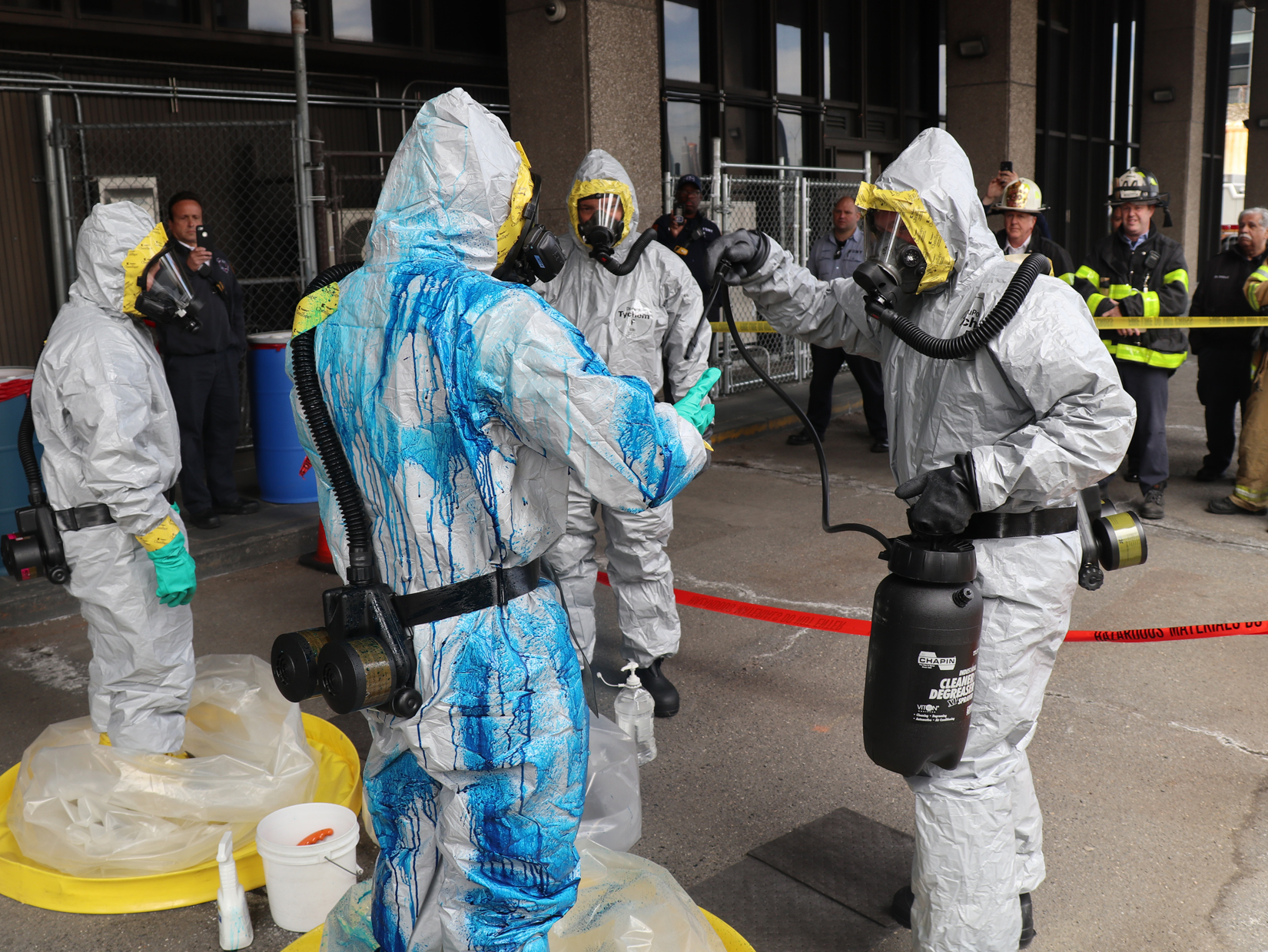 emergency responders dressed in haz-mat suits, with one covered in bleach, are spraying each other with liquids