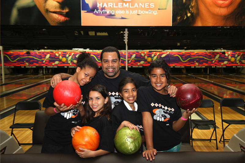 Family posing for picture with bowling balls at bowling alley