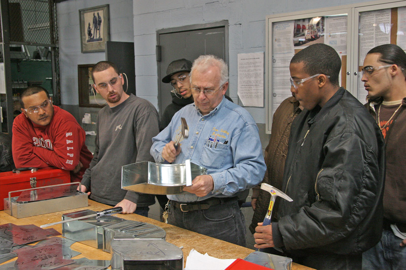 group of men watching teacher as he uses hammer