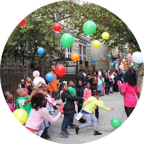 children playing with balloons on sidewalk in front of school