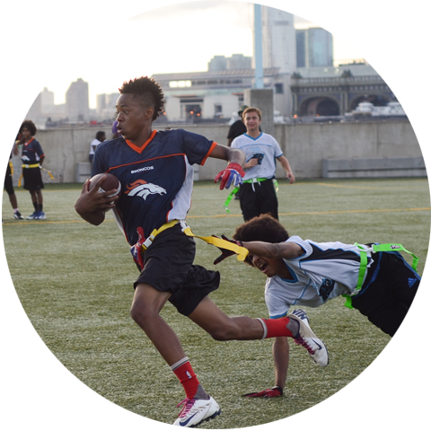 boys playing flag football on field