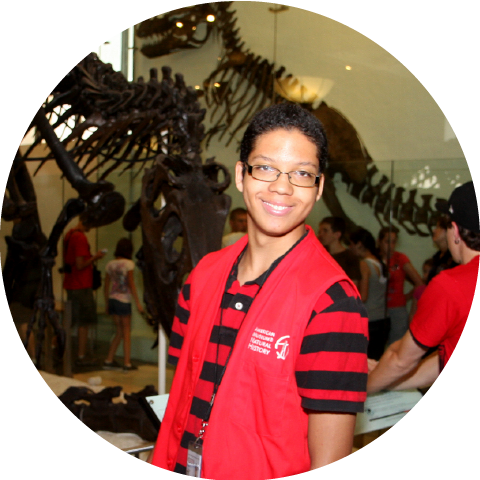 Student posing for picture in front of dinosaur skeletons