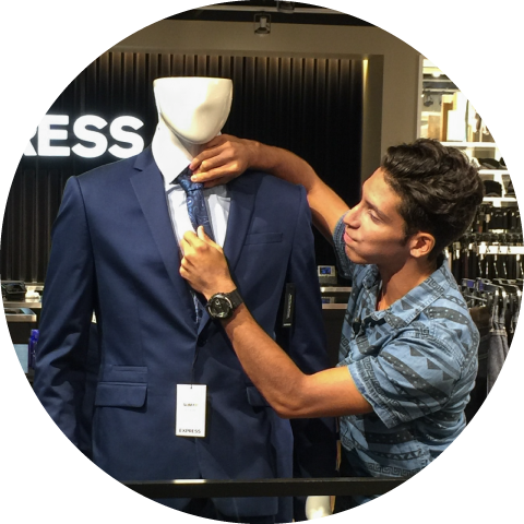 boy fixing tie on mannequin at Express clothing store