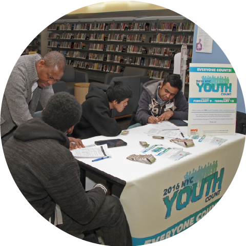 four males at table signup for 2016 NYC Youth Count