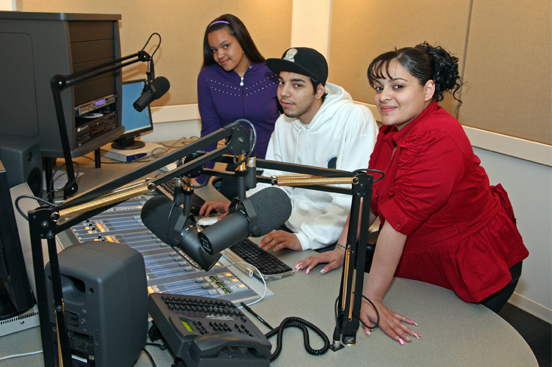 two girls and boy sitting in radio studio and posing for picture