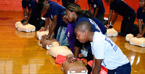 NYC youth practicing CPR during an FDNY workshop.