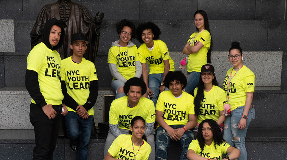 Teens showing off their NYC Youth Lead shits.