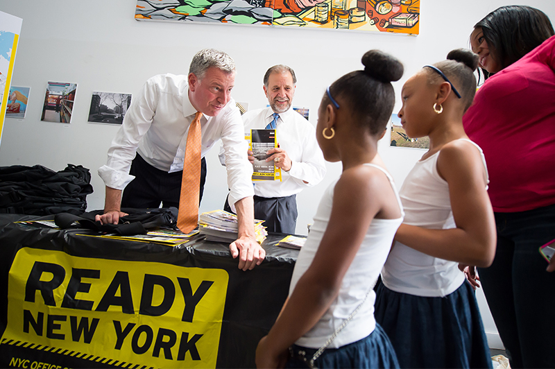 Mayor de Blasio speaks to a child at a Ready New York stand