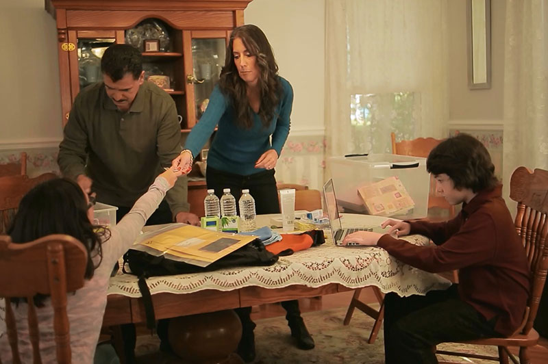 A family preparing for an emergency together at the dining room table of their home.
