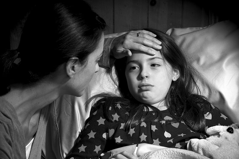 A black and white photo of a mother caring for her ill child, who is lying in bed.