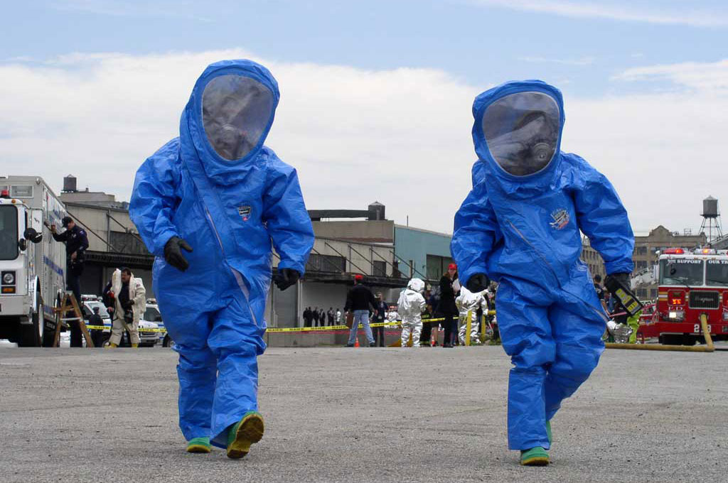 Two individuals wearing HAZMAT suits during a drill.