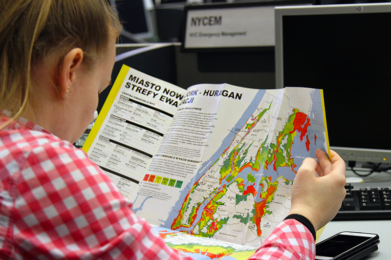 An individual reading the hurricane evacuation map in Polish.