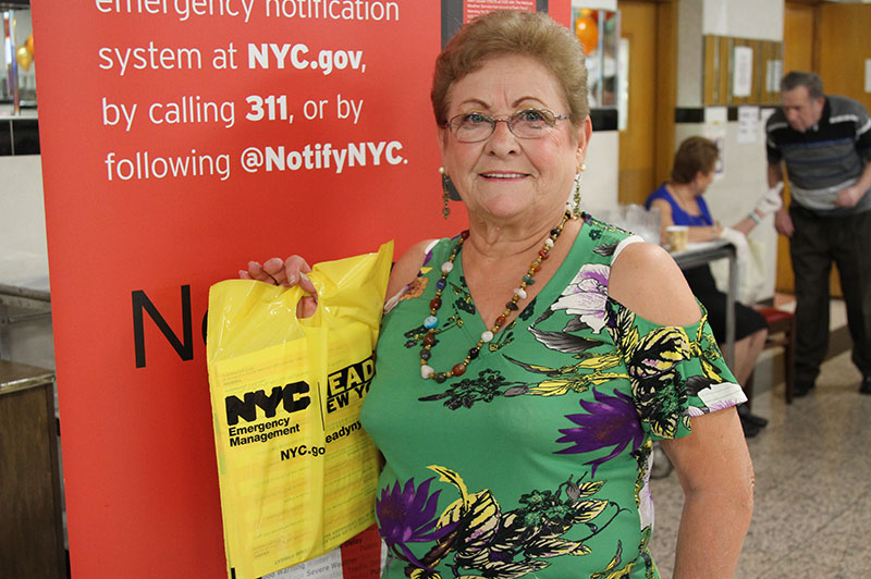 A senior citizen poses with Ready new York materials.