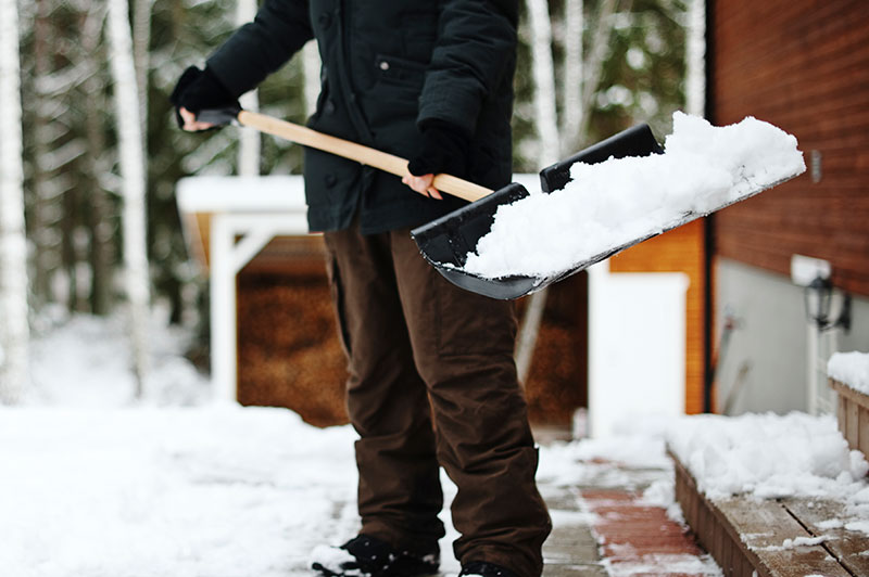 A person wearing cold weather gear holding a shovel with snow on it.