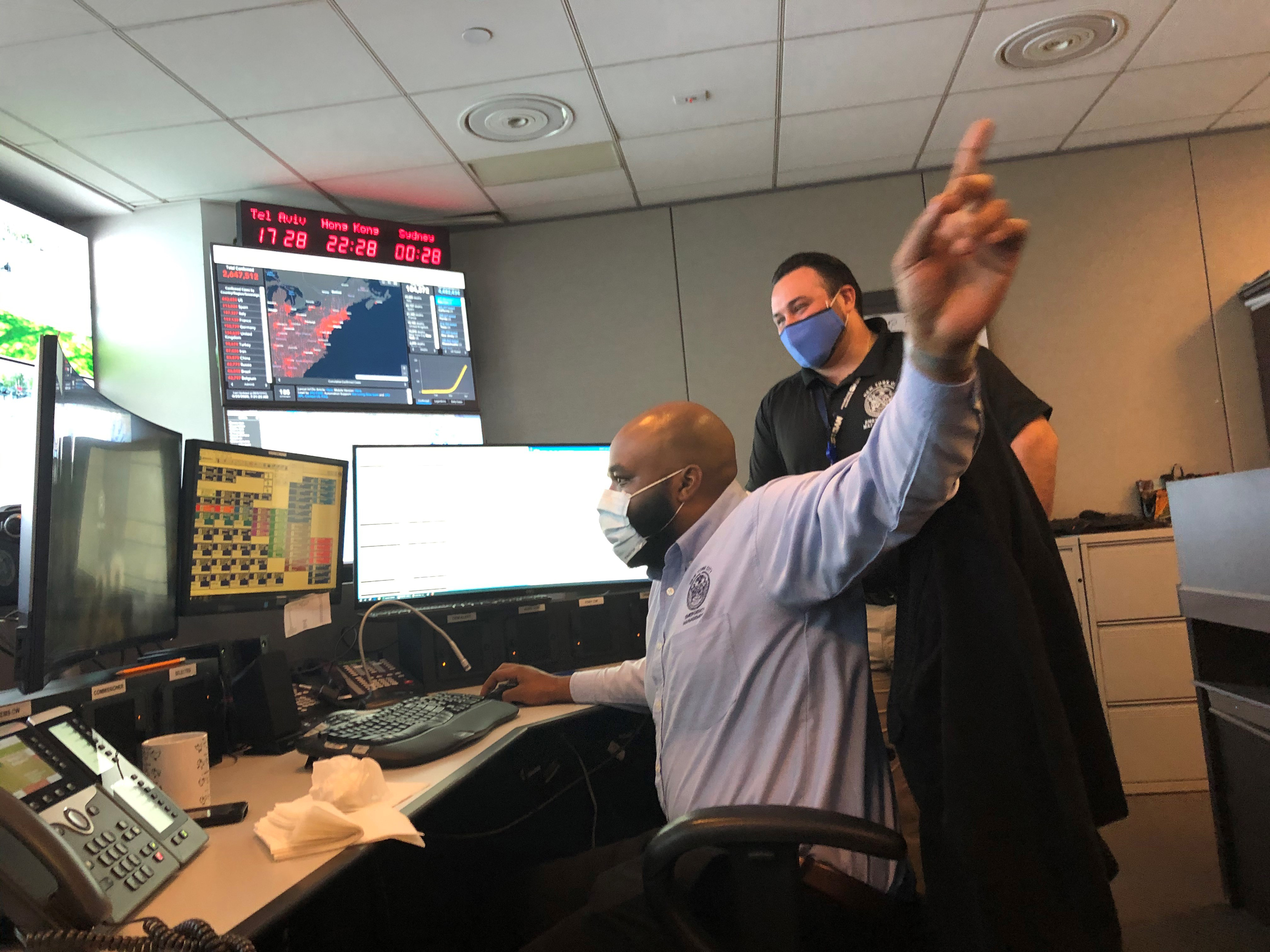 Torey Rowe (left) troubleshoots a desktop issue in NYC Emergency Management Watch Command.