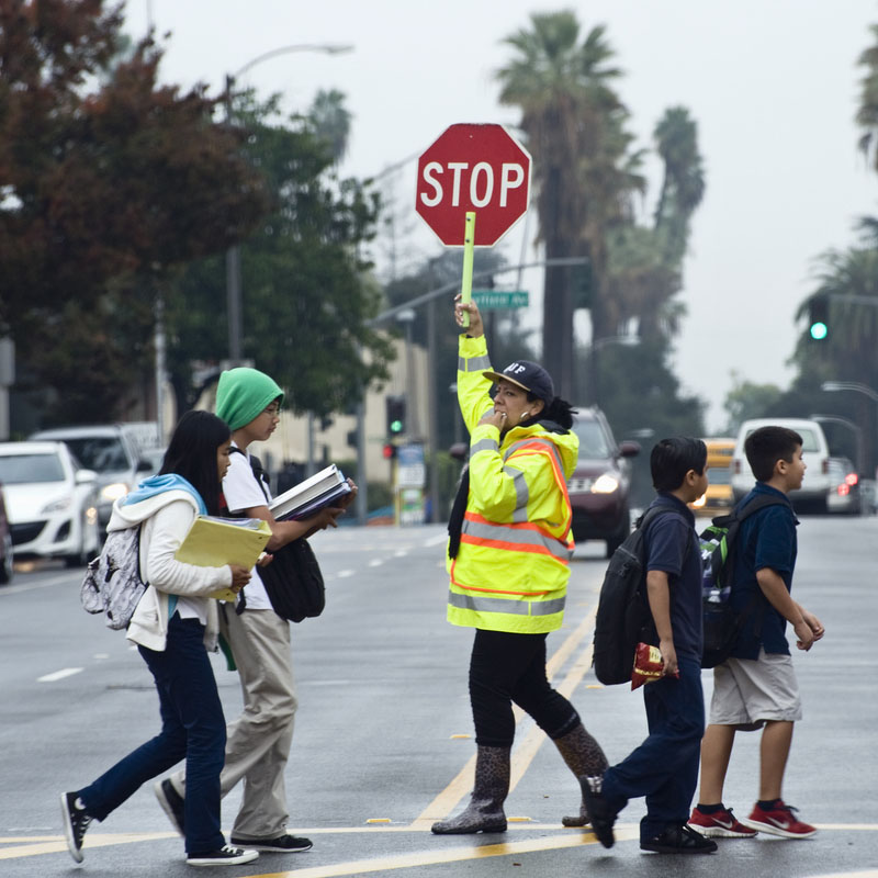Photo of crossing guard crossing children across a street while holding a stop sign