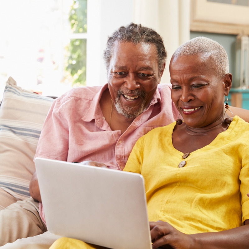 Photo of senior African American couple on sofa with laptop