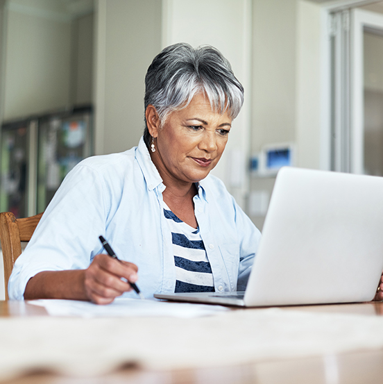 Photo of elderly woman using laptop and taking notes