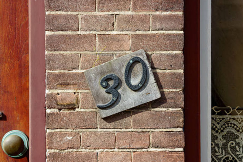 A plaque next to a door indicating the address is 30